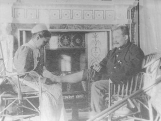 Black and white photograph showing a nurse dressing the foot of a soldier.