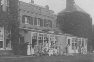 Black and white photograph showing the exterior and grounds on oakley VAD Hospital. Nurses and patients can be seen on the lawn.