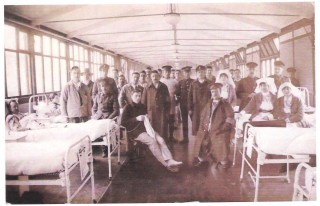 Sepia image showing staff and patients inside a ward at the Canadian Military hospital.